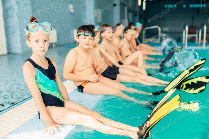 Children with colorful flippers sits near pool