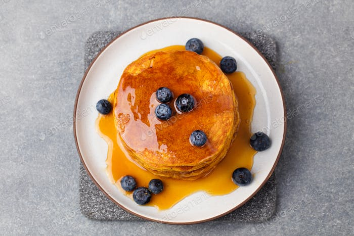 Pumpkin pancakes with maple syrup and blueberries on a plate. Grey stone background Top view