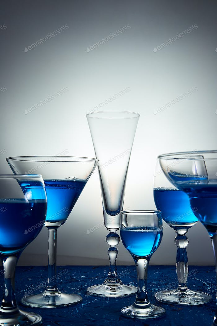 Many glasses with blue champagne or cocktail.