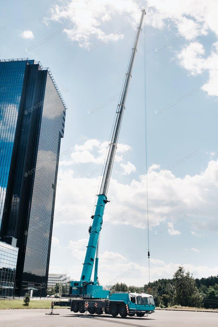 der höchste und größte blaue Autokran ist auf einer Plattform neben einem großen modernen Gebäude angelegt