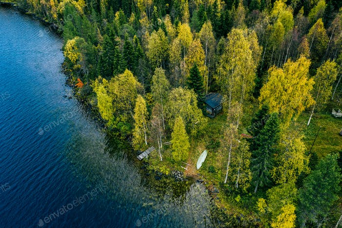 Aerial view of cottage in spring colors forest by the blue lake in rural  Finland