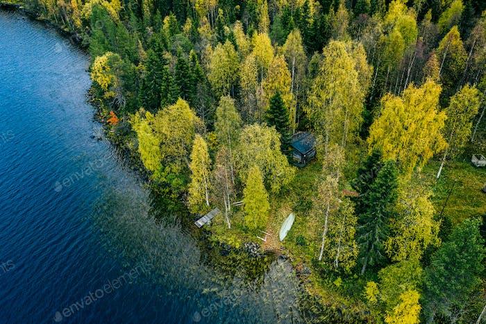 Luftaufnahme von Ferienhaus in Frühlingsfarben Wald am blauen See im ländlichen Finnland