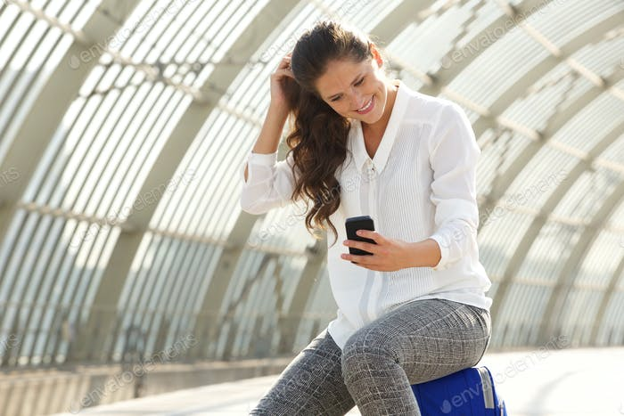 happy woman using smart phone at train station