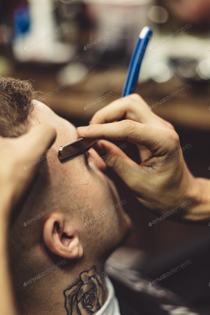 Crop stylist shaving client
