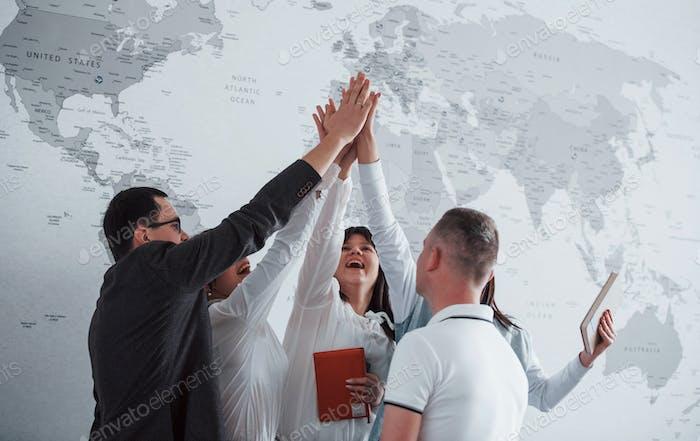 Team von Freiberuflern, die gegen die Mauer stehen, auf der Weltkarte