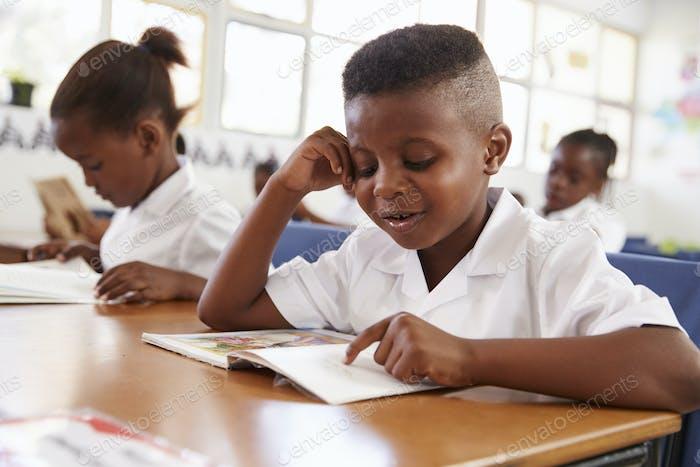 Grundschule Junge liest ein Buch an seinem Schreibtisch in der Klasse