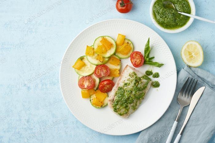 Keto Abendessen mit weißem Fisch. Ofen gebackenes Kabeljaufilet, Zander mit Gemüse und Pesto-Sauce
