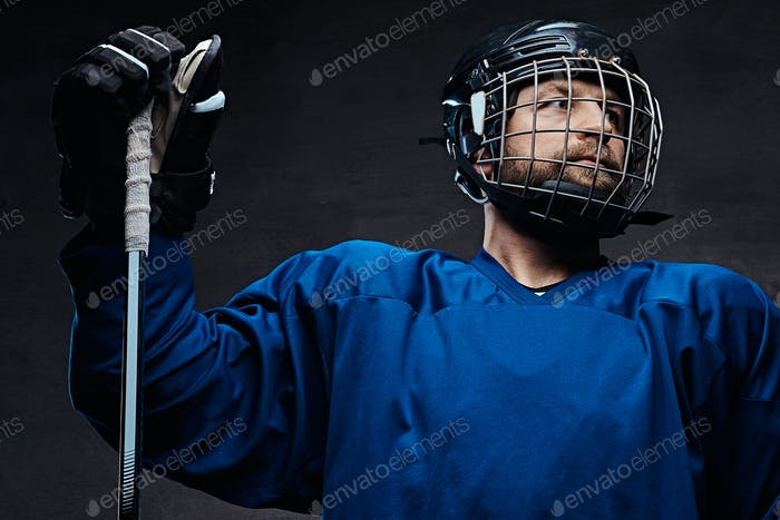 Portrait of a bearded ice-hockey player in a blue sportswear with gaming stick. Studio shot.