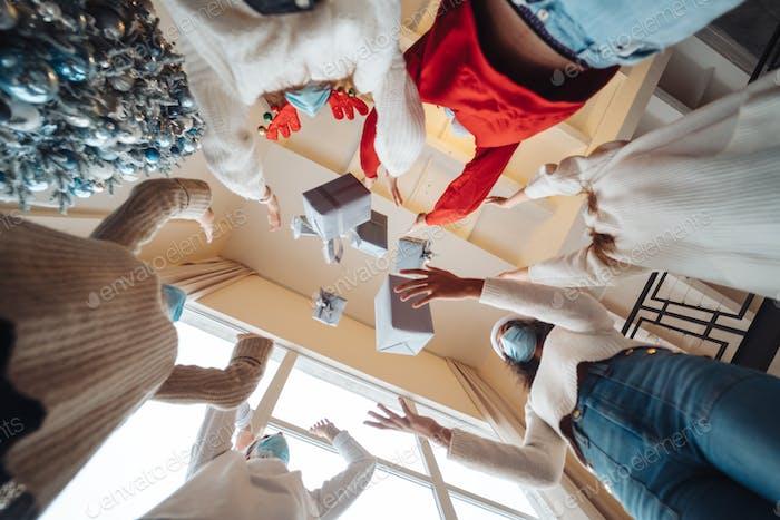 Многоэтнические друзья бросают свои рождественские подарки в воздух