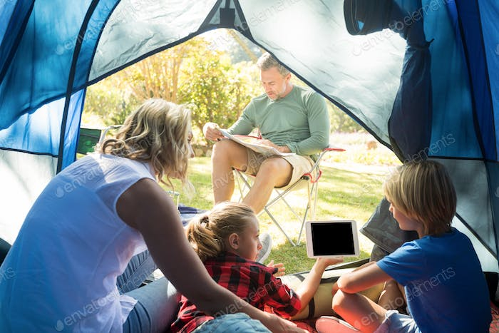 Kids and mother using tablet while father looking at the map