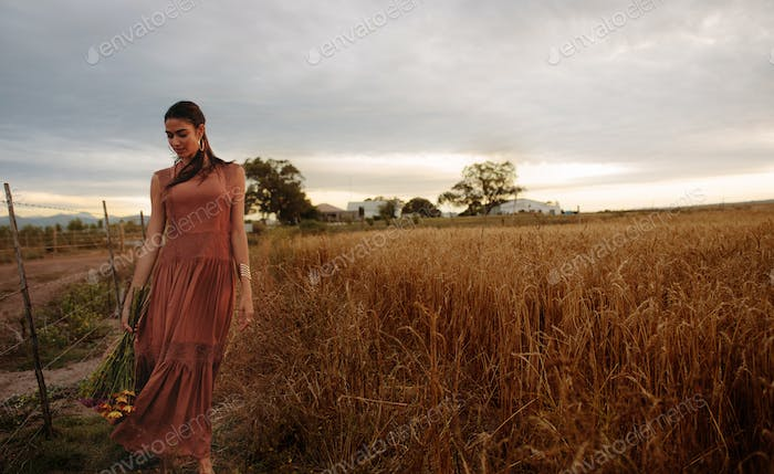 Woman strolling on wheat field with flowers