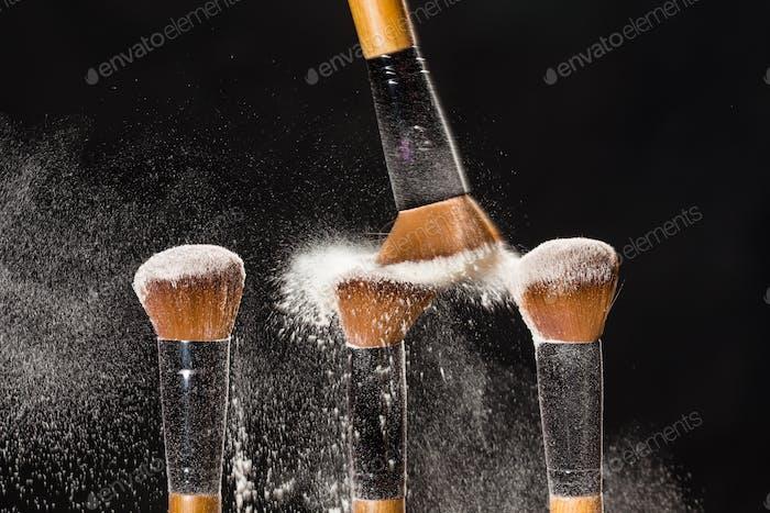 Make-up, Schönheit und Mineralpulver Konzept - Kosmetik Pinsel und Explosion bunte Make-up Pulver