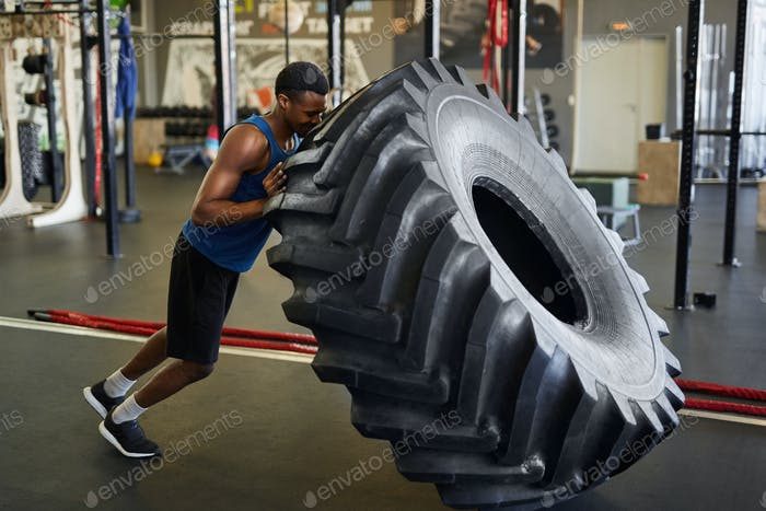 African Sportsman Flipping Tire in Gym