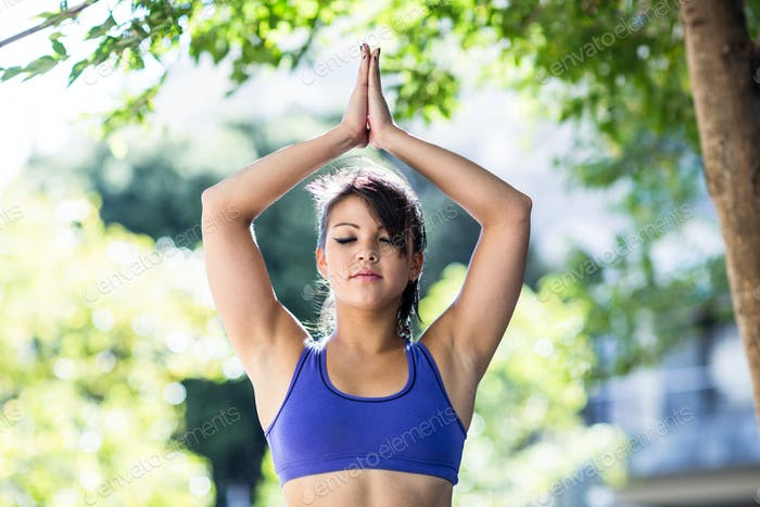 Peaceful athletic woman doing yoga in the city