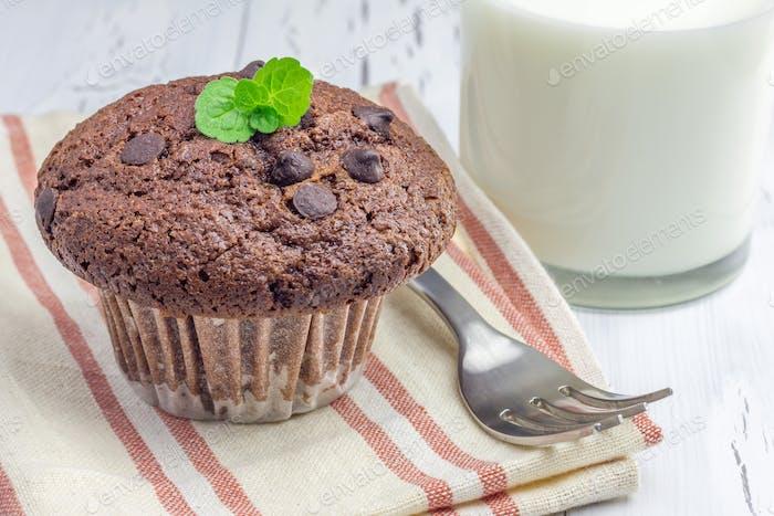 Köstlicher Schokoladenmuffin mit Choco-Chips und Glas Milch Nahaufnahme