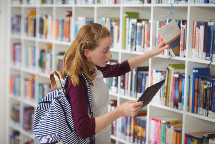 Schoolgirl using digital tablet while selecting book in library