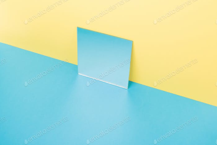 Mirror on blue table isolated over yellow background