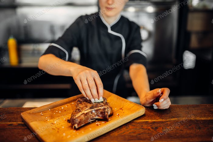 Ñook bestreuen frisch zubereitetes Steak mit Gewürzen