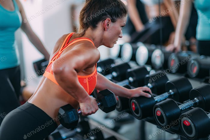 Attractive Female Athlete Exercising in the Gym