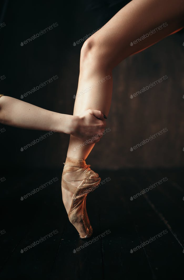 Ballerina hand holds the foot in pointe shoes