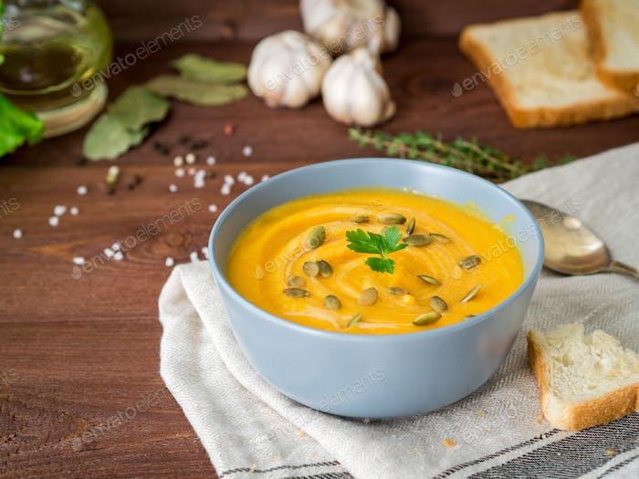 Crema dietética vegetariana Pupmkin puré de sopa, sobre mesa de madera marrón oscuro, vista lateral, de cerca.