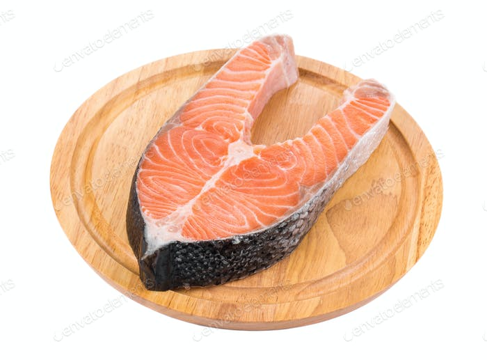 Raw salmon steak on cutting board.