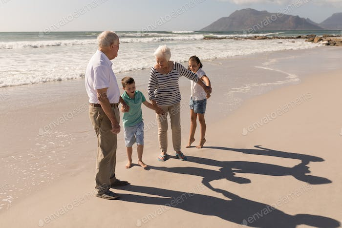 Side view of happy multi-generation family holding hands and having fun on beach in the sunshine