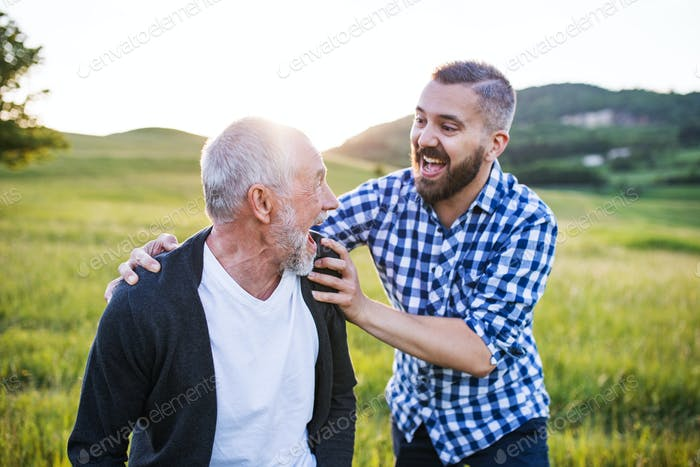 An adult hipster son with senior father on a walk in nature at sunset, having fun.