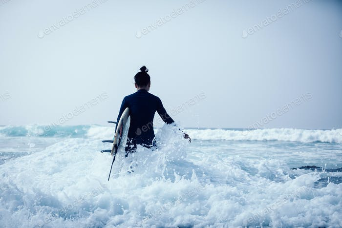Surfer with surfboard  in the waves