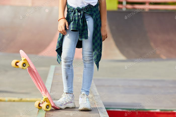 Girl with skateboard outdoors