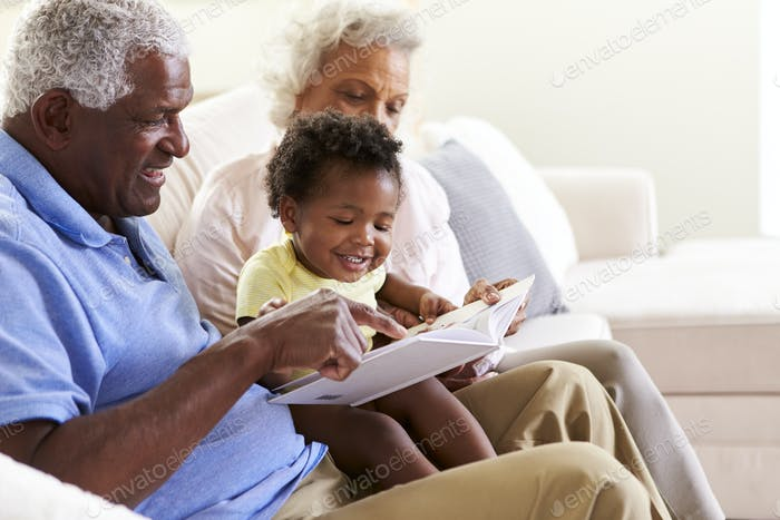 Grandparents Sitting On Sofa At Home With Baby Granddaughter Reading Book Together