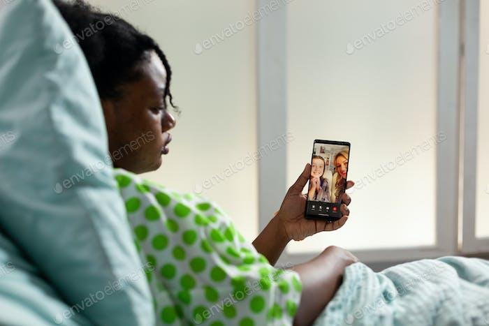 Patient of african american ethnicity using smartphone