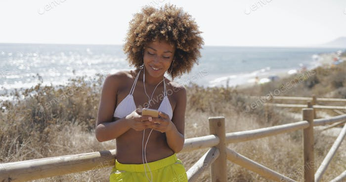 Charming girl using smartphone while training