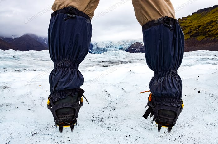 Mountaineer's feet with crampons on the frozen glacier, Vatnajokull