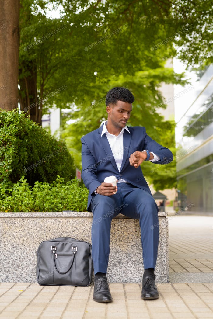 Portrait of African businessman checking time from wristwatch and holding take away coffee cup