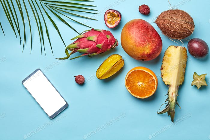 Mobile and various whole and halved tropical fruits with a palm leaf on a blue background with space