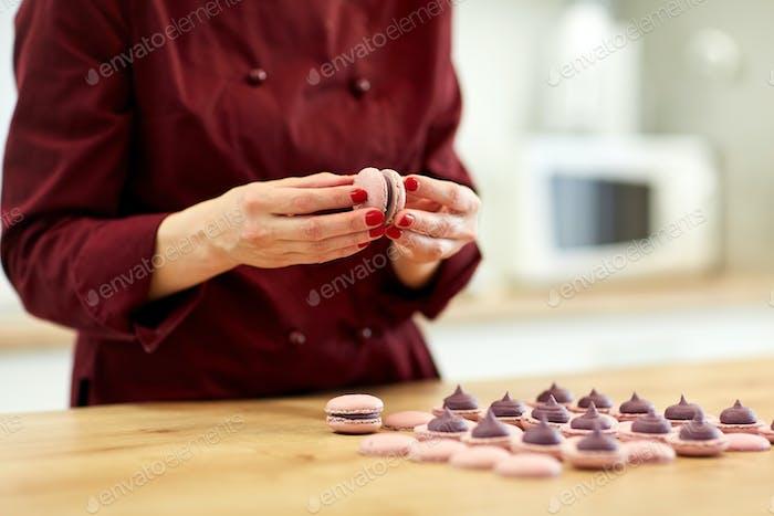 chef sandwiching macarons shells with cream