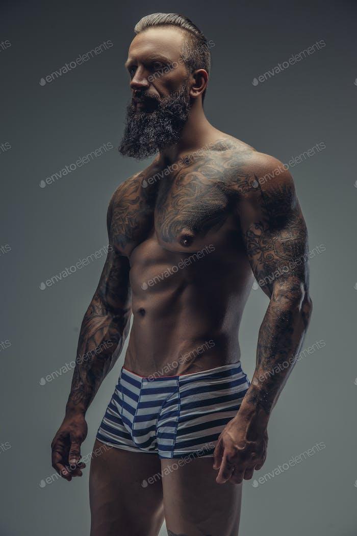 Мускулистый татуированный человек.