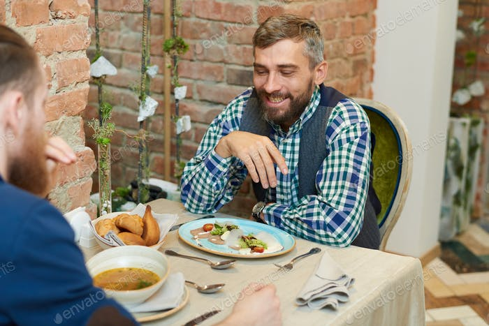 Handsome Mature Man Enjoying Meal in Restaurant