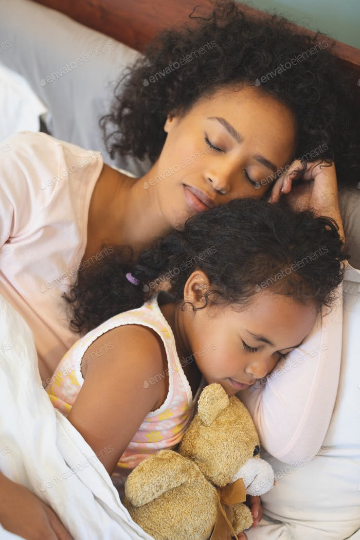 Close-up of African American mother and daughter sleeping together on bed in bedroom at home