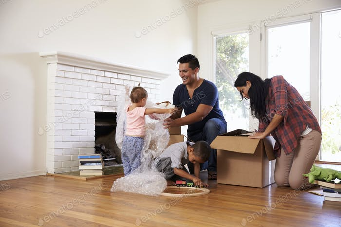 Family Unpacking Boxes In New Home On Moving Day