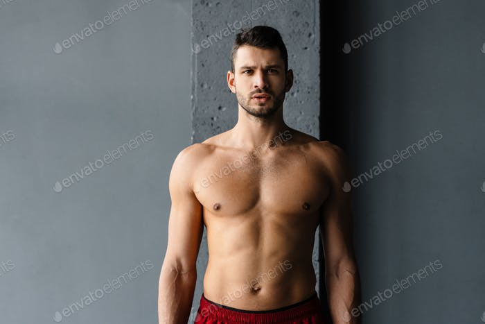 Young shirtless sportsman looking at camera while working out indoors