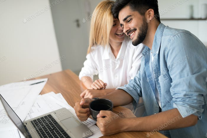 Photo of cheerful loving young couple using laptop