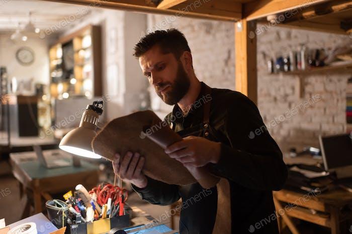 Bearded craftsman examining piece of leather