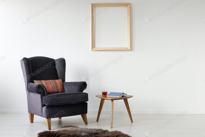 Empty wooden frame on white wall of elegant living room with com