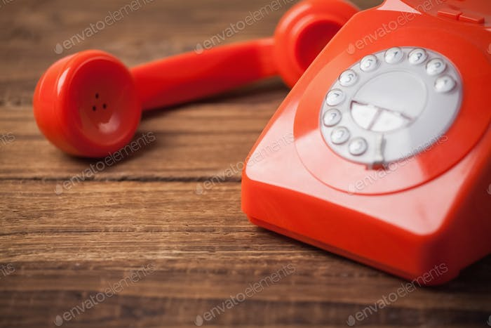 Red telephone on wooden table with copy space