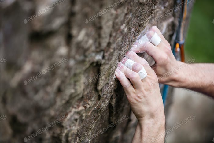 Rock climber's hands gripping small hold on natural cliff