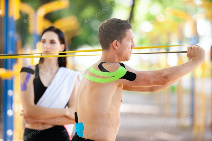 Man and woman with kinesiological taping training outdoors