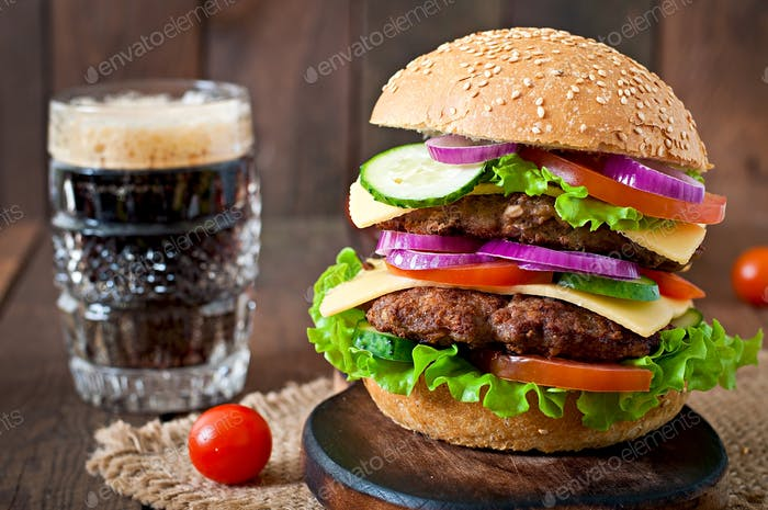 Big juicy hamburger with vegetables and beef on a wooden background in rustic style