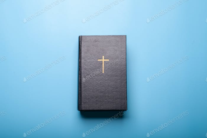 black holy bible on bright blue background
